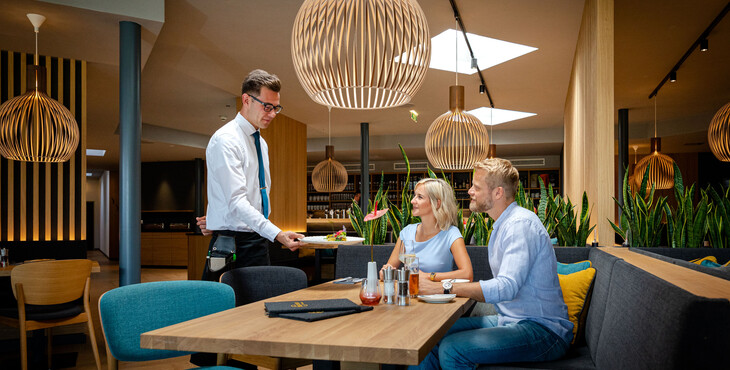 Ein Kellner serviert einem Paar im Restaurant bei Villach das Essen