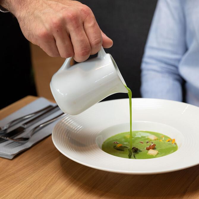 Ein Kellner serviert das Essen im Restaurant zum Frühstücken und Brunchen in Villach Umgebung