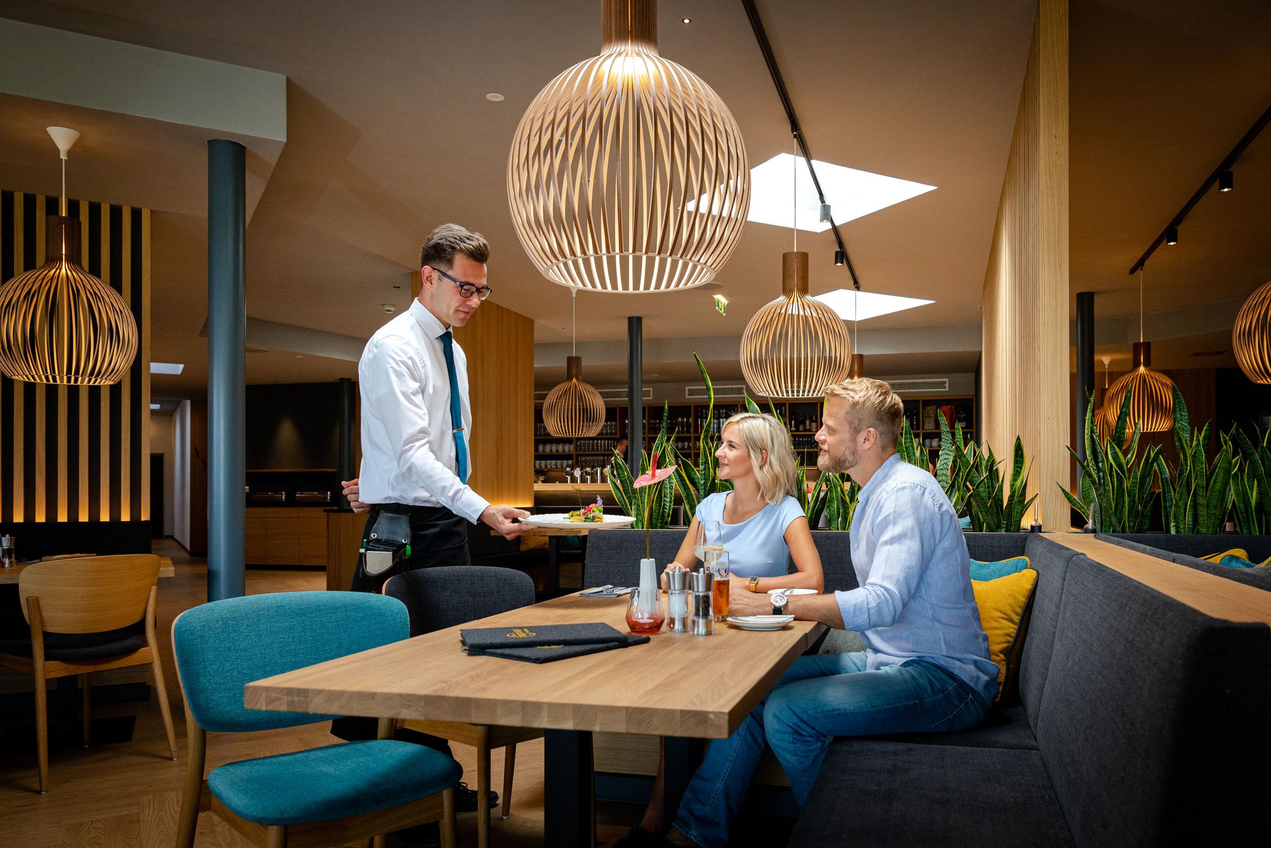 Ein Kellner serviert einem Paar das Essen im Gasthaus in Villach Umgebung