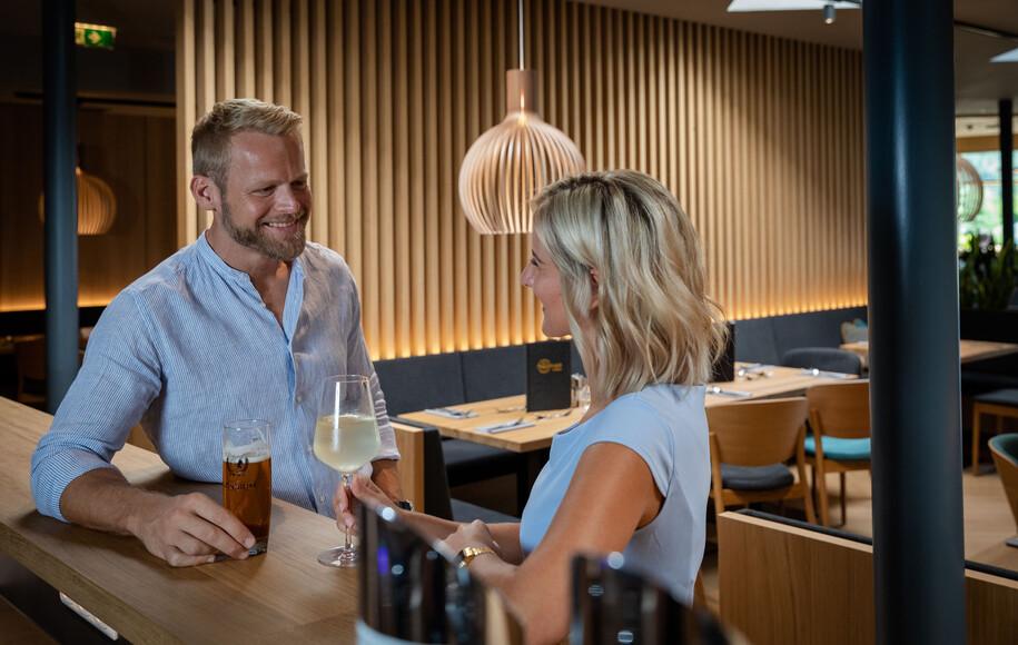 Ein Paar genießt einen Drink an der Bar im Restaurant bei Villach
