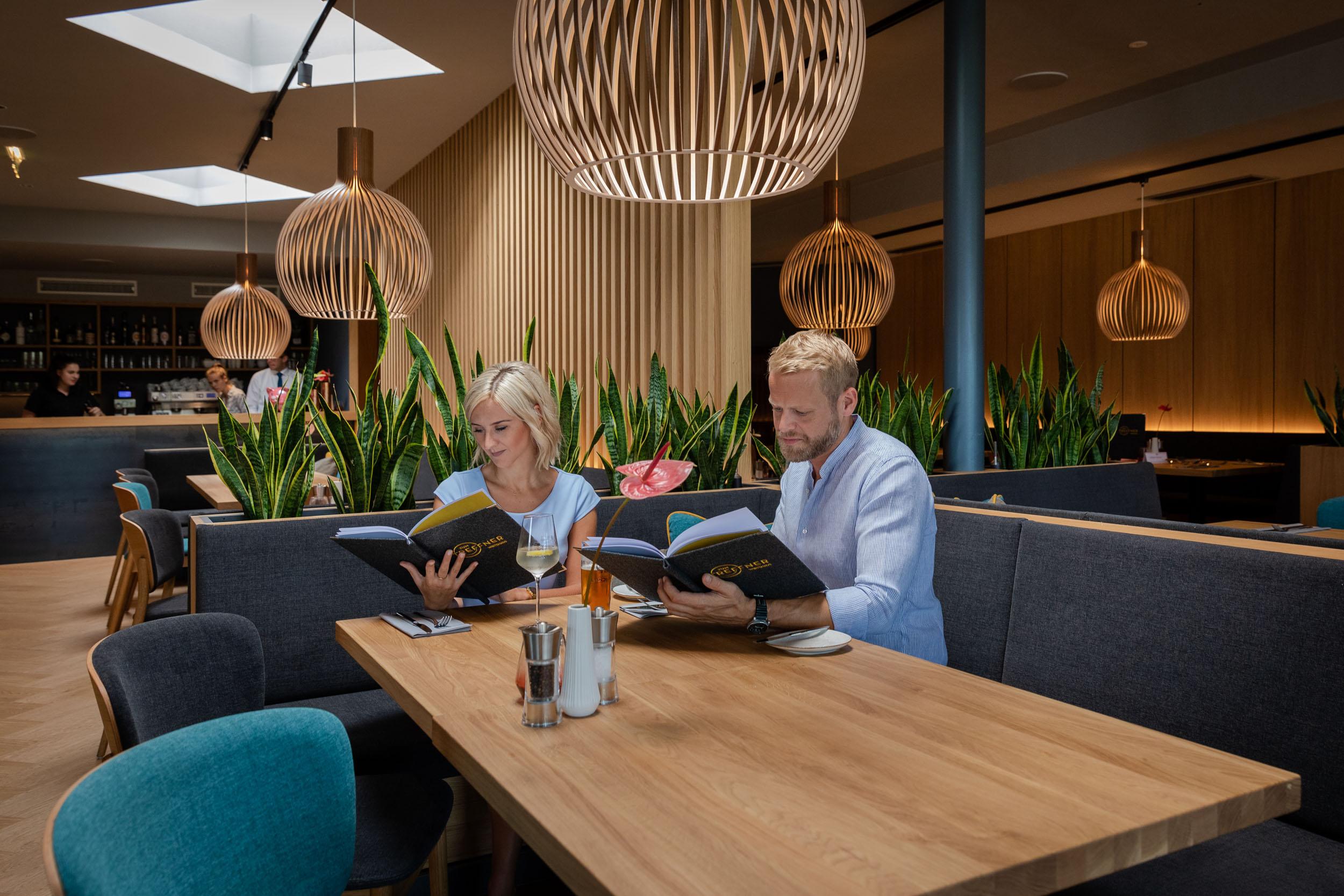 Ein Paar studiert die Speisekarte im Wirtshaus zum TREFFNER