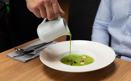 Einem Gast des Gasthauses in Villach Umgebung wird die Suppe eingeschenkt