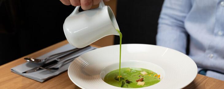 Ein Kellner schenkt im Restaurant bei Villach einem Gast die Suppe ein