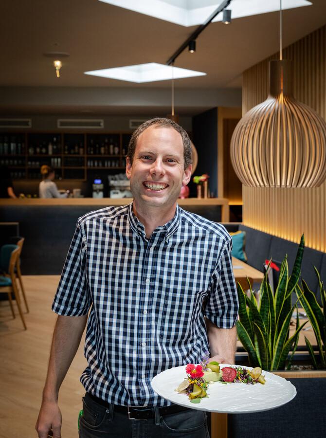 Der Gastgeber serviert im Gasthaus in Villach Umgebung einen liebevoll angerichteten Teller